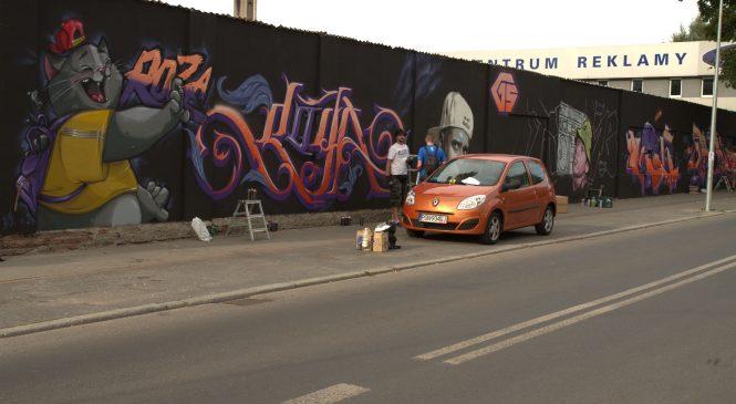Wielkie graffiti wita podróżnych wysiadających na dworcu